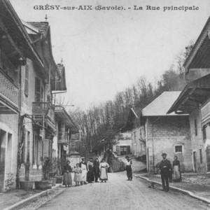 Sous la Tour, rue principale avec tous ses commerces. La maison à droite avec le balcon en bois était l'habitation de M. François Fort décédé en 1982, donateur à la commune.